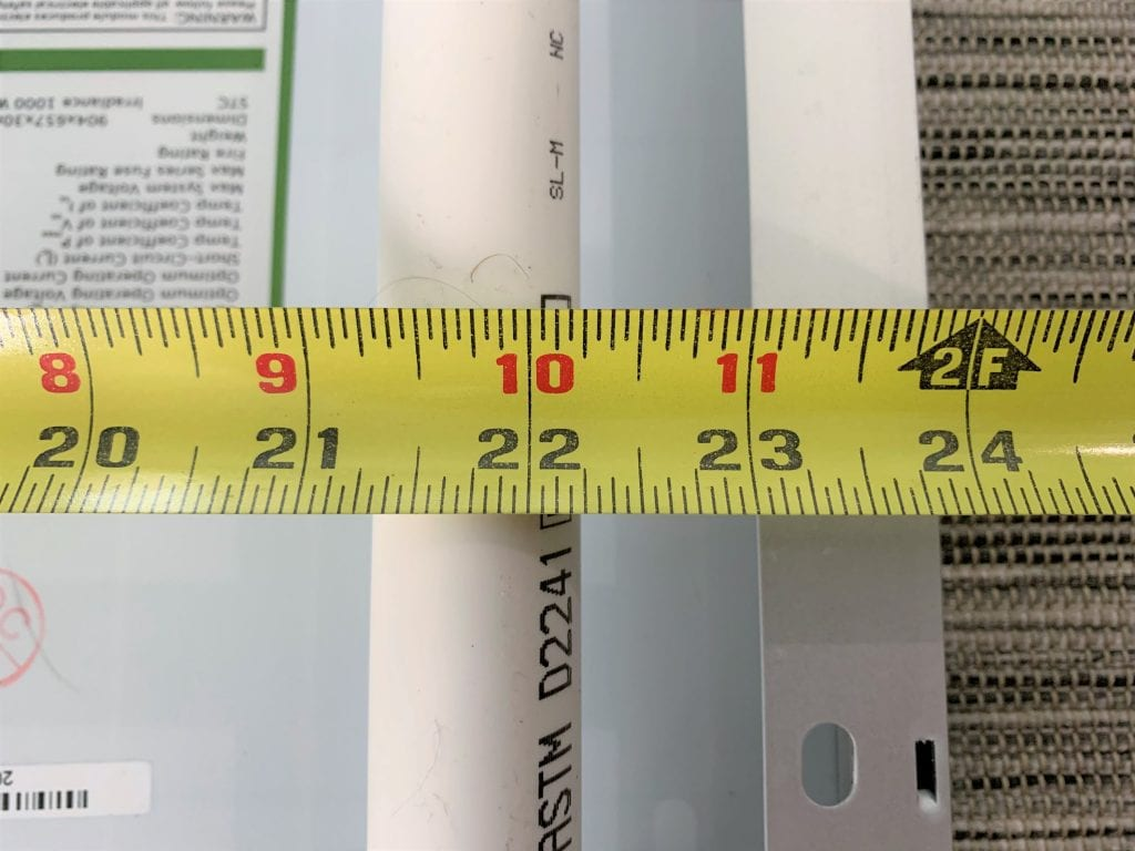 "A yellow tape measure measuring 22.25"" with a PVC pipe and metal rim in the background"
