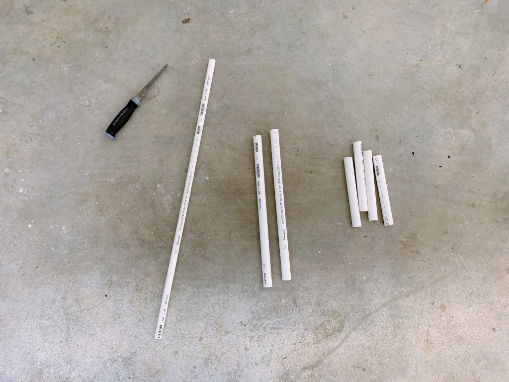 Seven sections of PVC pipe of varying sizes and diameters and a handsaw laying on the ground