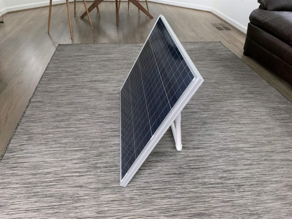 An HQST solar panel with a homemade solar panel stand mounted in a living room