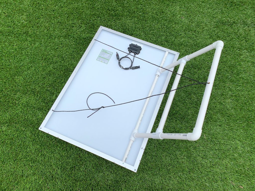 A solar panel with a portable solar panel mount laying upside down on astroturf