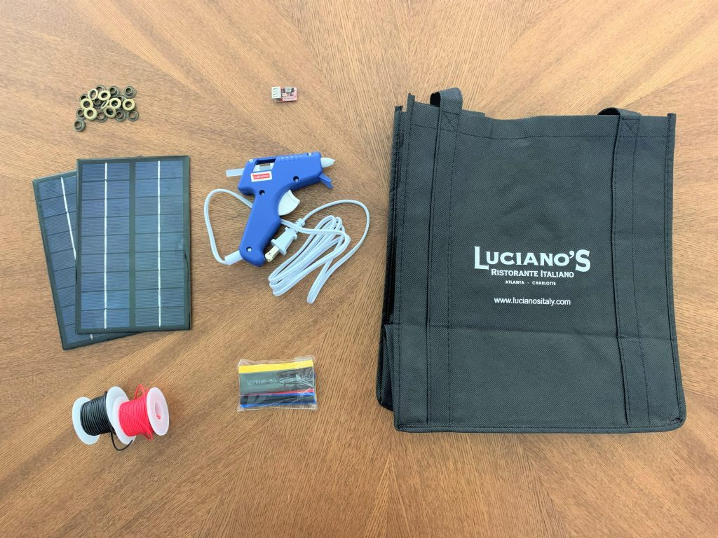 Materials for building a DIY solar USB charger laid out on a wooden table