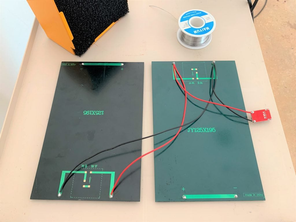Two solar panels wired to a 5-volt USB buck converter