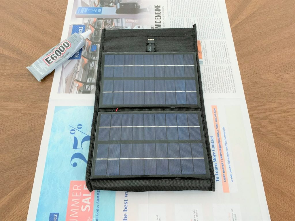Solar panels glued to a strip of fabric laid on top of a piece of newspaper