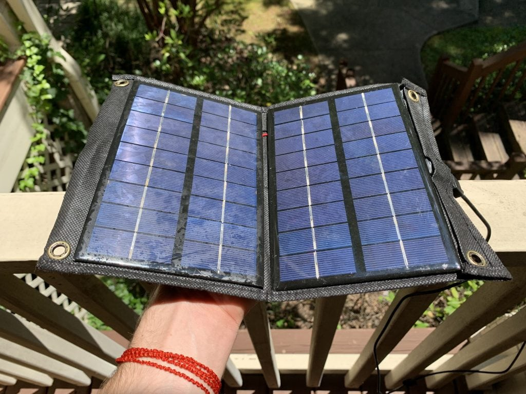 A solar charger being held in direct sunlight on a balcony