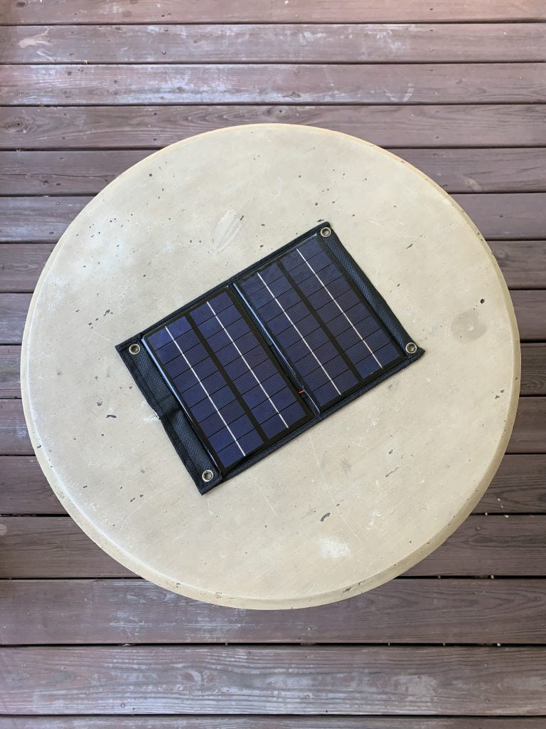 A DIY solar charger resting on a table on a balcony