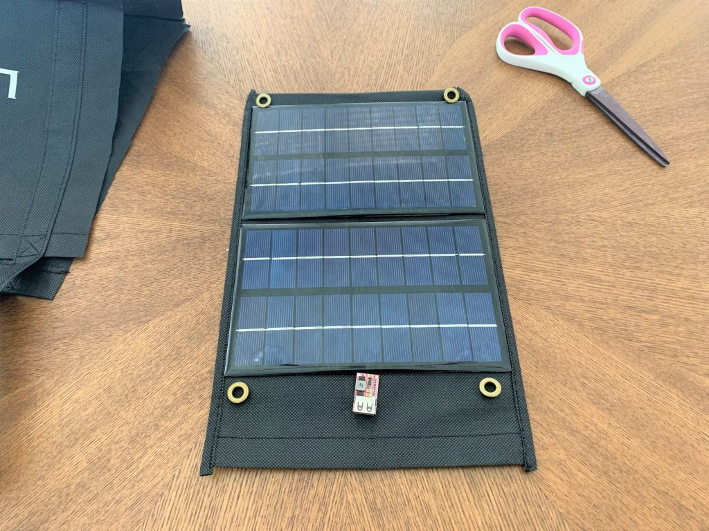 Two 3W 9V solar panels, four eyelets, and a USB buck converter laid on a strip of cut fabric