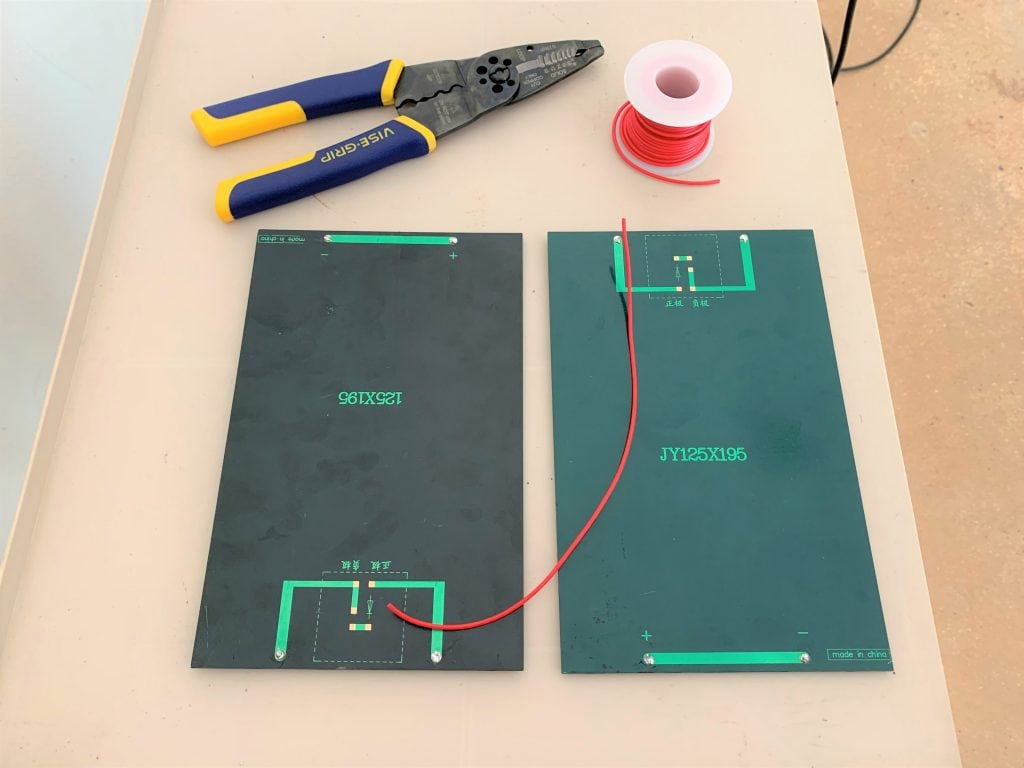 Two 3W 9V solar panels, a length of red wire, a roll of red wire, and wire strippers laid on a surface
