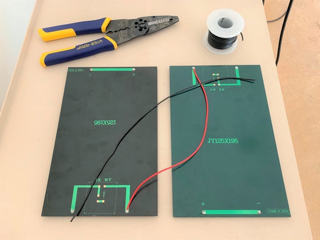 Two small solar panels, a length of black wire, a roll of black wire, and wire strippers laid out on a surface